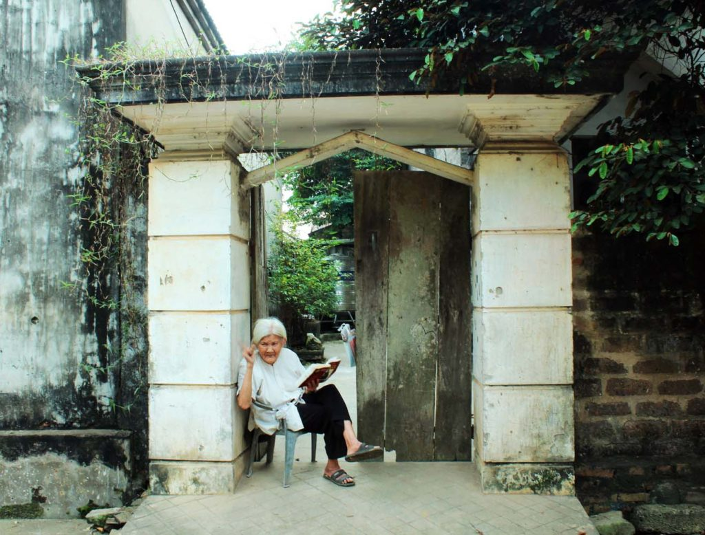 Old lady sitting in front of her ancient house in Duong Lam ANcient Village