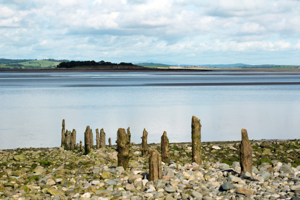 The calm cobblestone beach at Manjushri KMC Ulverston